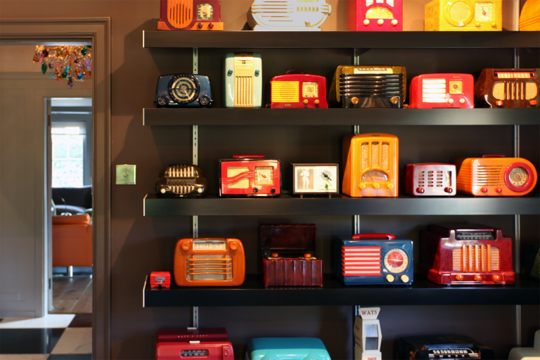 Black wall shelving and anodised silver wall fixings are used to display vintage radios