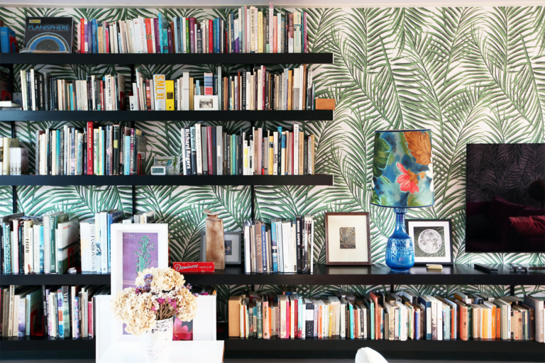 Black wall shelving system combined with bold wallpaper