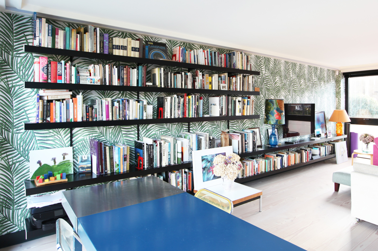 Black wall shelves and fixings combined with bold wallpaper