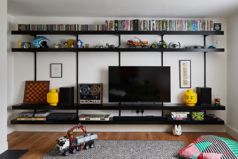 ON&ON black shelving system with single shelves 4m in length, designed to hold a 50inch tv screen and for storing toys and games