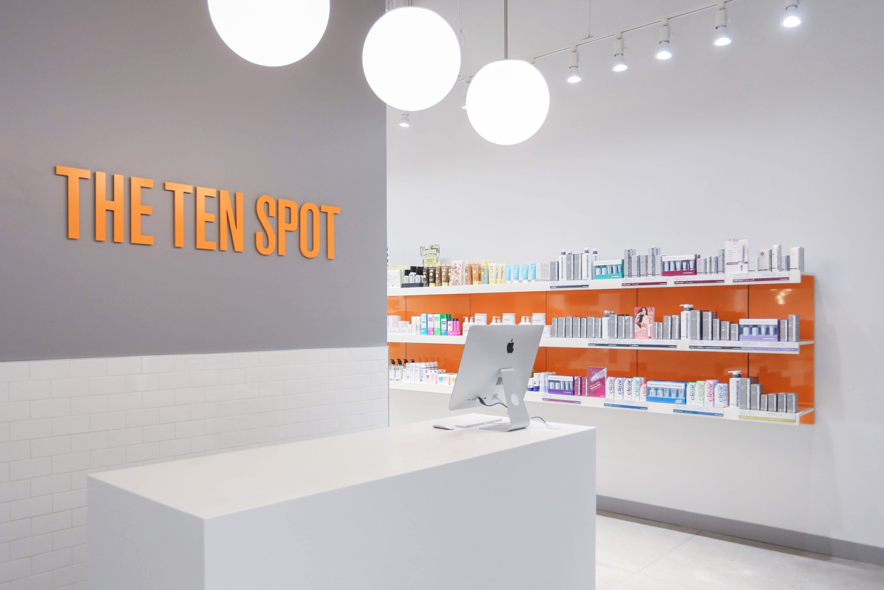 Beauty bar display shelving with orange wall panels
