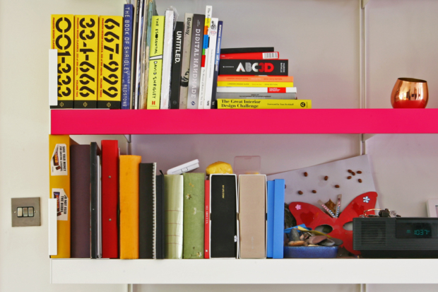 A bright pink bespoke shelf colour combined with a white shelving system