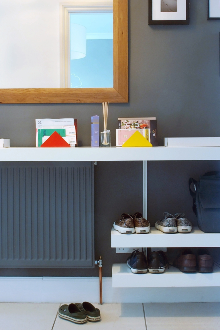 Hallway storage designed at low level but also around an existing radiator