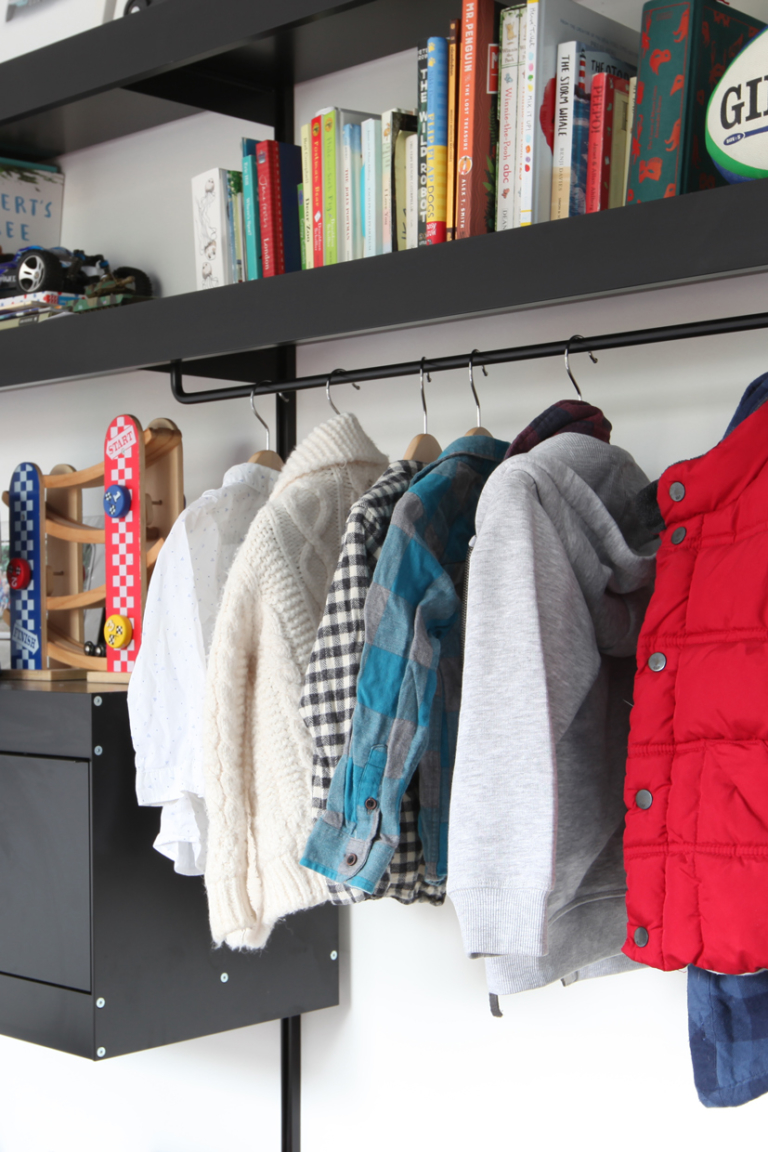 Wall shelving system with black shelves and clothes hanger